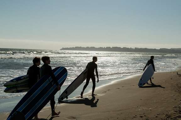 Surfers drag their boards behind them as they troll Stinson Beach, Calif., Saturday, May 23, 2015.