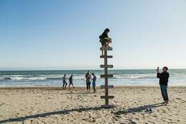 Chet Weiner, right, takes a photo of his son Laish Doris-Weiner, 9, as he climbs atop a wood ladder in the sand in Stinson Beach, Calif., Saturday, May 23, 2015.