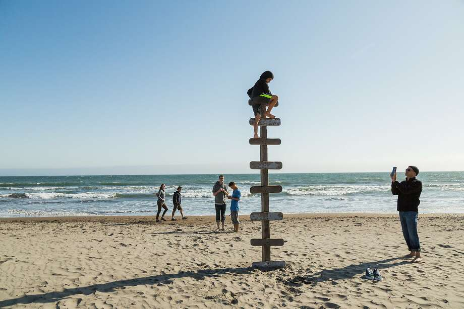 Chet Weiner, right, takes a photo of his son Laish Doris-Weiner, 9, as he climbs atop a wood ladder in the sand in Stinson Beach, Calif., Saturday, May 23, 2015. Photo: Jason Henry, Jason Henry For Medium