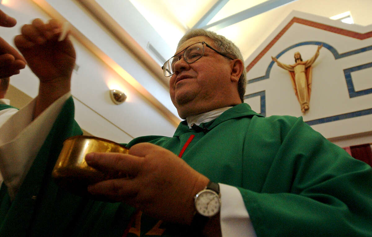 METRO Father Virgilio Elizondo hands out communion at St Rose LIma, Sunday, August 25, 2002. GLORIA FERNIZ/STAFF