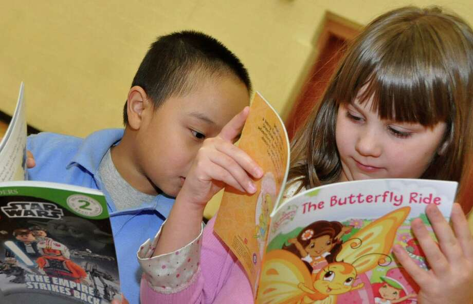 Jackson Co, left, checks out Kaitlyn Kokinda's book as volunteers from UGI, in partnership with the Reading is Fundamental (RIF) children's literacy organization, read to first grade students at Heights-Terrace Elementary/Middle School Wednesday, Jan. 28, 2015, in Hazleton, Pa. During the program students were allowed to choose a book to keep and also received a coloring book to read and color. Through this volunteer program, UGI hopes to promote reading and lifelong learning skills for children. (AP Photo/Hazleton Standard-Speaker, Ellen F. O'Connell) Photo: Ellen F. O'Connell, MBR / Associated Press / Hazleton Standard-Speaker