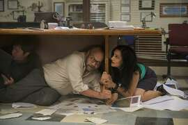 """This photo provided by Warner Bros. Pictures shows Paul Giamatti as Lawrence and Archie Panjabi as Serena, in a scene from the action thriller, """"San Andreas."""" The movie releases in theaters on May 29, 2015.  (Jasin Boland/Warner Bros. Pictures via AP)"""