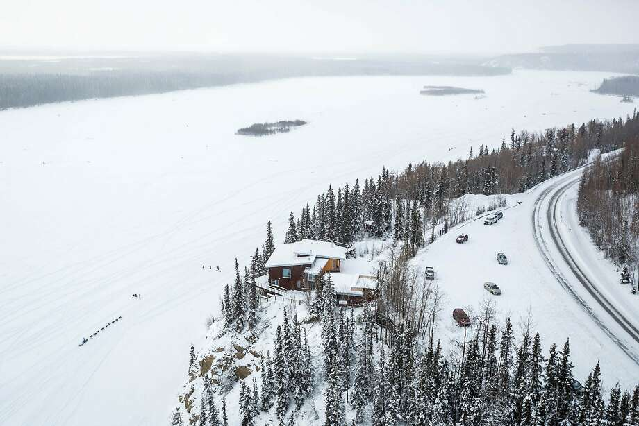 In this aerial photo a dog team mushes past a house above the Tanana River during the start of the Iditarod Trail Sled Dog Race, Monday, March 9, 2015, in Fairbanks, Alaska. Iditarod mushers began their 1,000-mile trek across Alaska along a new route Monday after poor trail conditions forced organizers to push the race's start north, bypassing a mountain range.(AP Photo/Alaska Dispatch News, Loren Holmes) Photo: Loren Holmes, Associated Press