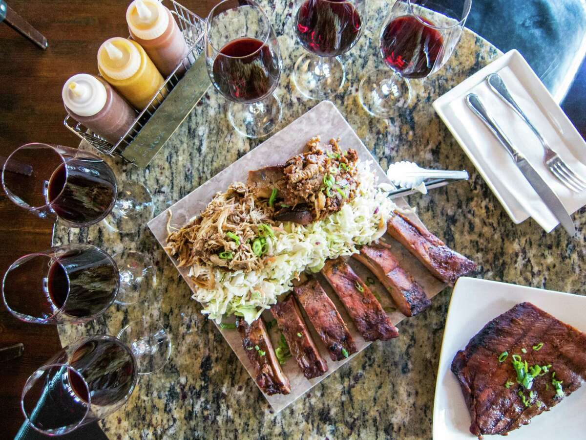 A table filled with a flight of wine pairings as well as brisket, pork ribs and pulled pork at the Bounty Hunter Wine Bar & Smokin' BBQ in Napa, Calif.