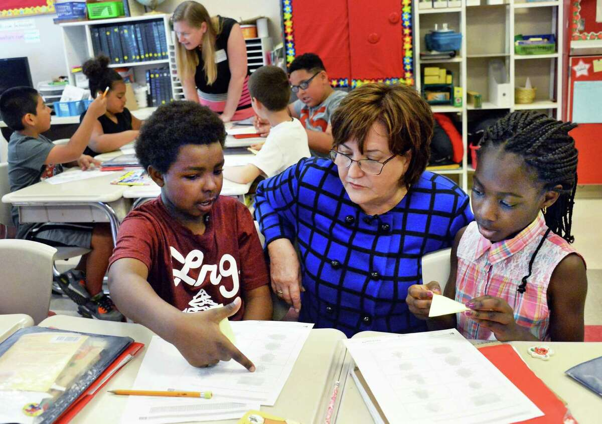Newly appointed NYS Education Commissioner Maryellen Elia, center, with third graders Sekel Babb, left and Taneecia McNeill during a visit a Pine Hills Elementary School Wednesday May 27, 2015 in Albany, NY. (John Carl D'Annibale / Times Union archive)