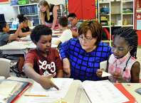 Newly appointed NYS Education Commissioner Maryellen Elia, center, with third graders Sekel Babb, left and Taneecia McNeill during a visit a Pine Hills Elementary School Wednesday May 27, 2015 in Albany, NY.  (John Carl D'Annibale / Times Union)