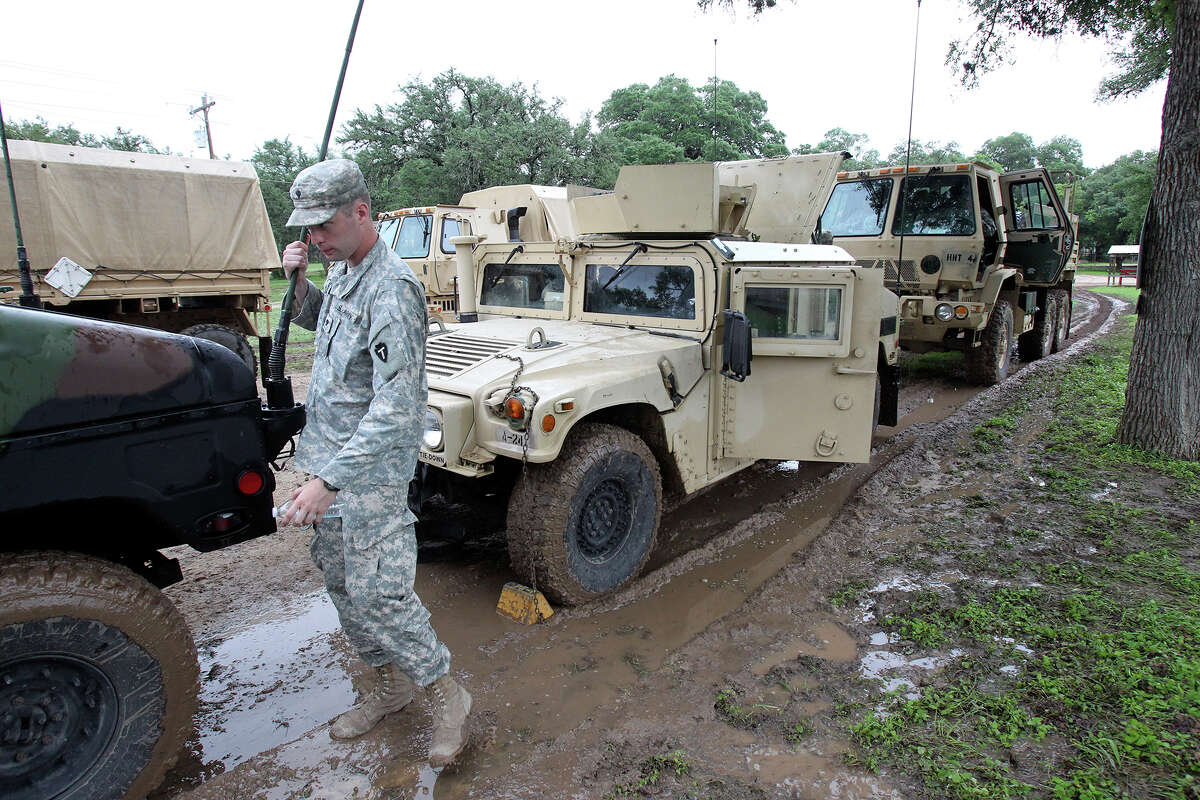 With more rain falling, a military vehicles stops to regroup in a parking lot as clean up continues in Wimberly after devastating flooding of the Blanco River with Texas National Guard troops still assisting with search and rescue on May 27, 2015.
