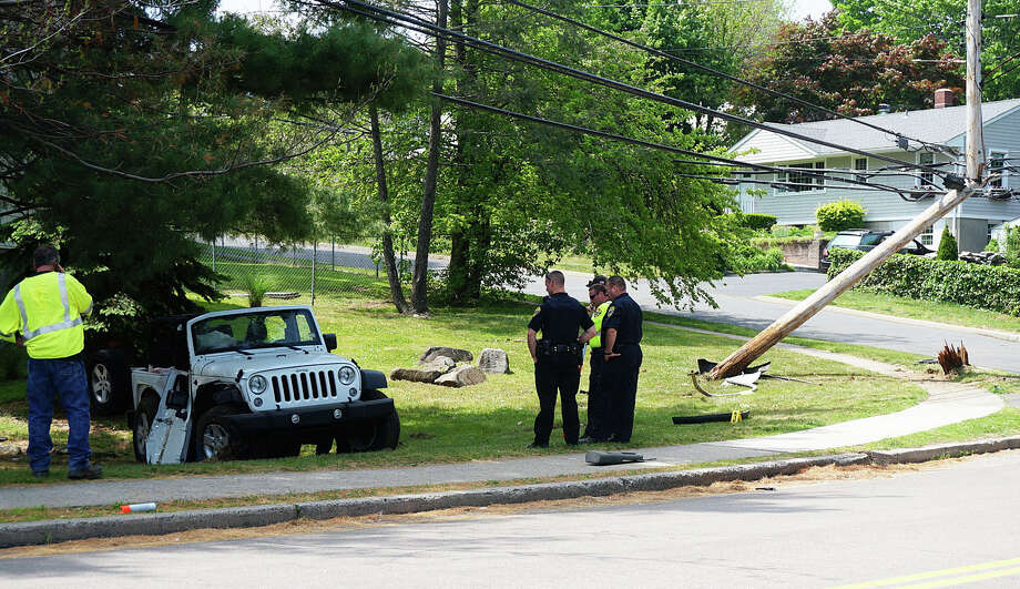Police investigate the scene of a Wednesday morning accident where two Fairfield Warde High School students were injured when their Jeep smashed into a utility pole on Knapps Highway, snapping it in half. Photo: Genevieve Reilly / Fairfield Citizen