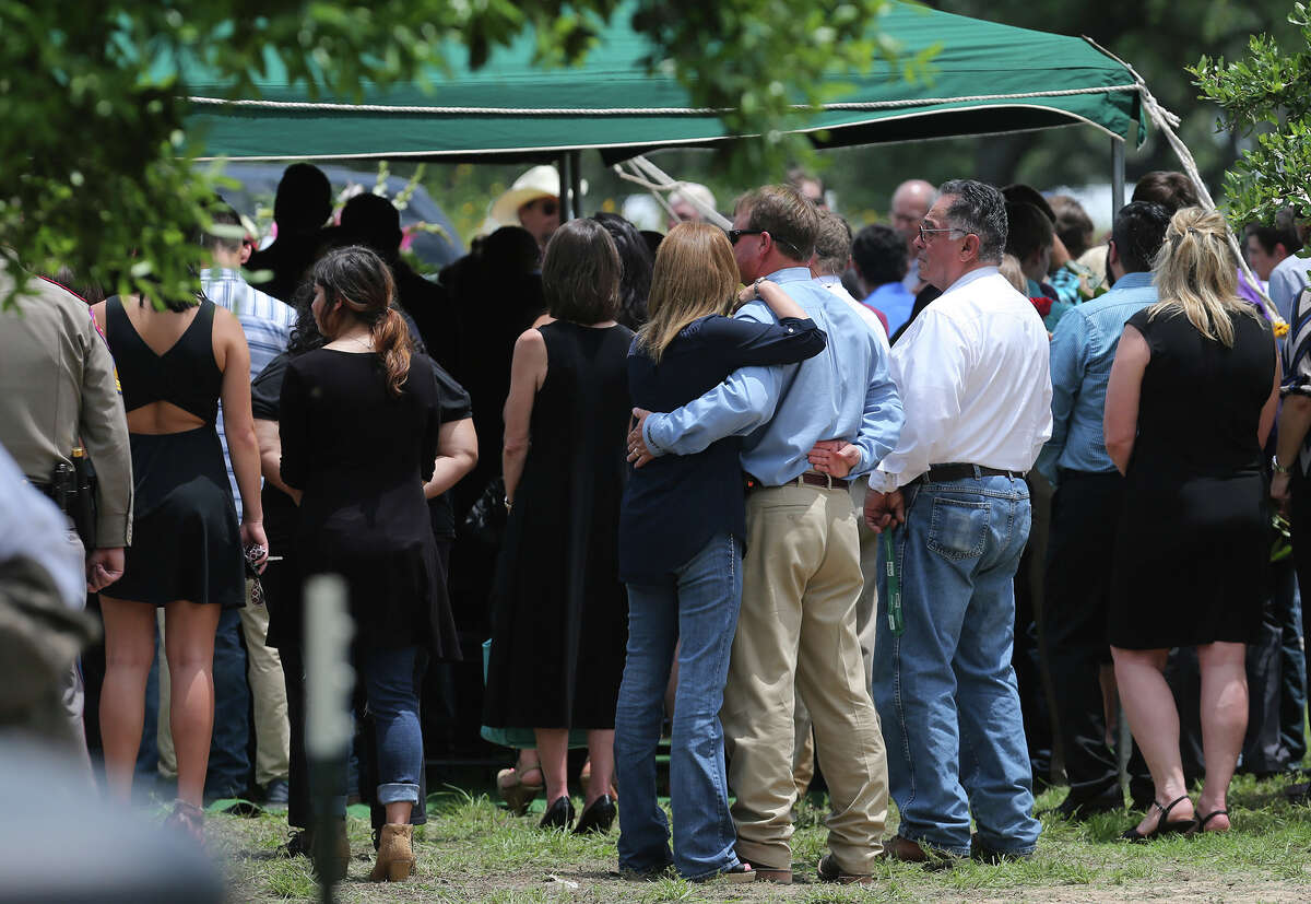 Mourners gather Wednesday May 27, 2015 at the Devine Evergreen Cemetery for the graveside service of Devine High School graduating senior Alyssa Ramirez. Ramirez died in last weekend's storms after her car stalled in rising floodwaters near Devine, Texas.