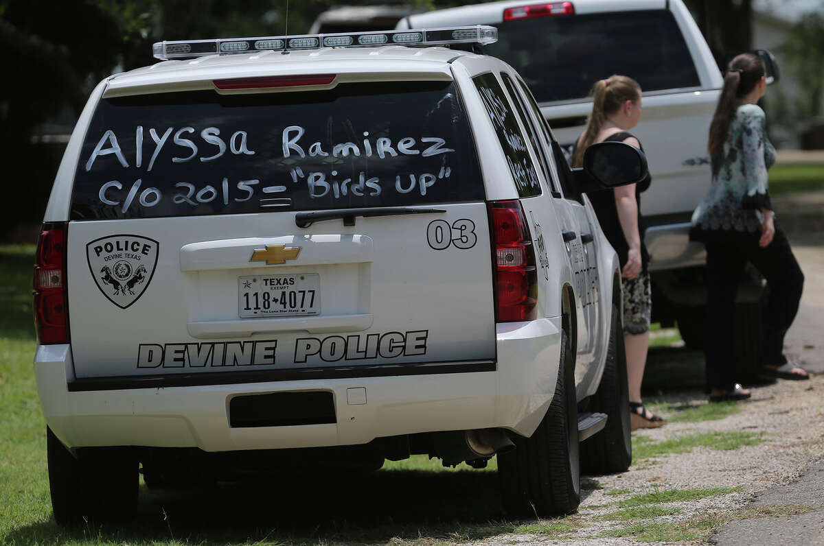 A Devine, Texas police vehicle has words written on it Wednesday May 27, 2015 regarding Devine High School graduating senior Alyssa Ramirez who died in last weekend's floods. The car was parked at the Devine Evergreen Cemetery for Ramirez's graveside service.