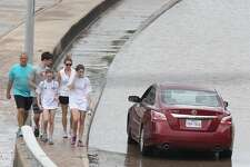 People walk Memorial Drive looking at the flood damage and flooded cars on Tuesday, May 26, 2015 in Houston, TX  (Photo: Thomas B. Shea/For the Chronicle)