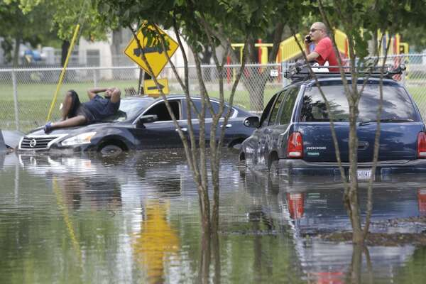 Marcus Williams, left, and Robert Flores, right,  wait on top of their cars surrounded by water on South Gessner near South Bissonnet Tuesday, May 26, 2015, in Houston. It took more than 8 hours for them to both to be towed. ( Melissa Phillip / Houston Chronicle )