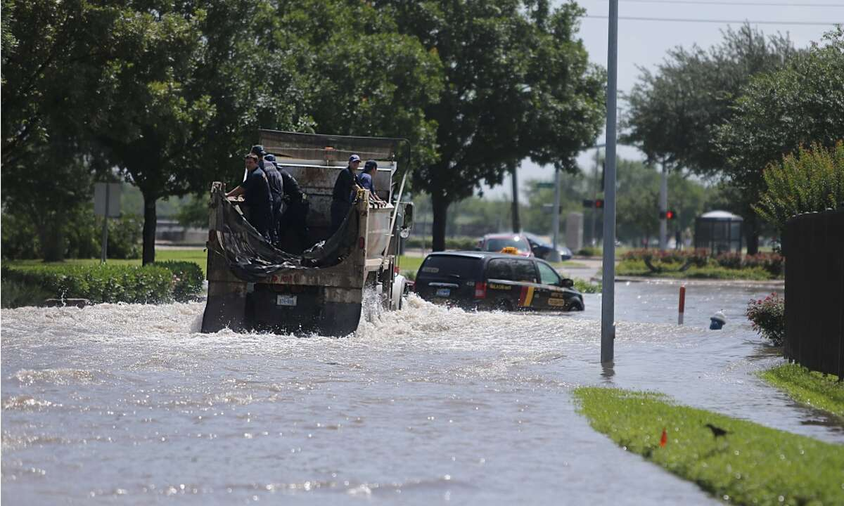 Houston Fire Fighters drive into flooded South Braeswood at Fondren. Brays Bayou is now within its banks, but neighborhoods are still flooded on Tuesday, May 26, 2015, in Houston. ( Mayra Beltran / Houston Chronicle )