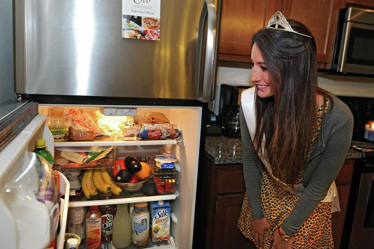 Alexandra Cronin looks into her refrigerator at her home on Wednesday, May 20, 2015 in Selkirk, N.Y. Alexandra is the most recently crowned Tulip Queen. (Lori Van Buren / Times Union)