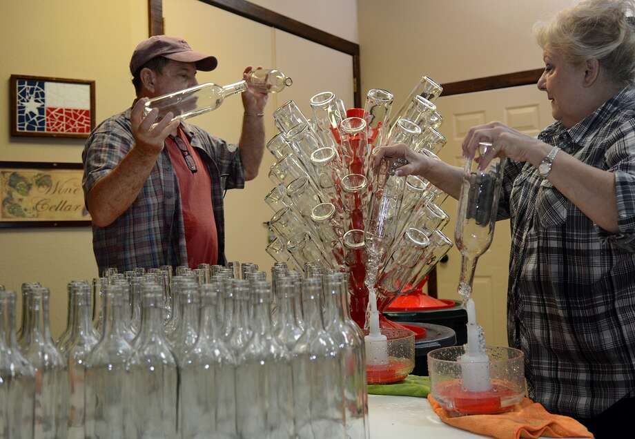 Jerry Bernhardt, from left, owner of Bernhardt Winery, and Glenda Hodges, of Montgomery, work the bottle washing station during the wine-bottling session at Bernhardt Winery in Plantersville on Thursday, May 21, 2015. (Photo by Jerry Baker/Freelance) Photo: Jerry Baker, Freelance
