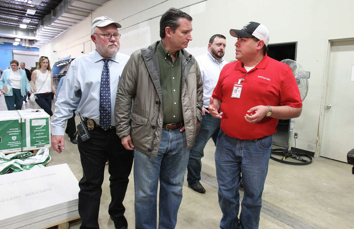 San Marcos Mayor Daniel Guerrero chats with Senator Ted Cruz after he speaks at the San Marcos Police Department after taking a tour of flood devastation in the area on May 27, 2015. Trailing is Hays County Judge Bert Cobb.
