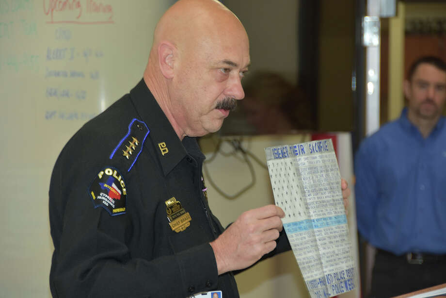 Chief of Police Alan Bragg displays a poster with names of fallen officers created by Cypress Creek High School freshman Jason Fischer. Fischer sent the token of remembrance to the CFISD police officers on behalf of Officer Greg Loter, who previously worked at Cypress Creek. Photo: Cy-Fair American Federation Of T
