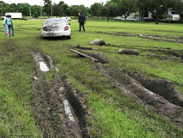 Deep muddy ruts lead to a car stuck in a field Wednesday, May 27, 2015, in Houston. Several attempts at removal just added to the mess. The death toll from a barrage of storms and floods in Texas and Oklahoma climbed to at least 19 on Wednesday, with over a dozen people missing, and another round of rain threatened to complicate the cleanup in hard-hit Houston.  (AP Photo/Pat Sullivan) ORG XMIT: TXPS104 Photo: Pat Sullivan / AP