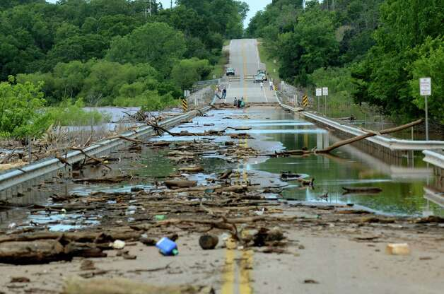 Debris sits on the Twin Bridges as water recedes from Lake Thunderbird Tuesday, May 26, 2015, after heavy rains hit Norman, Okla., over the weekend.  (Kyle Phillips/The Norman Transcript via AP) ORG XMIT: OKNOT101 Photo: Kyle Phillips / The Norman Transcript