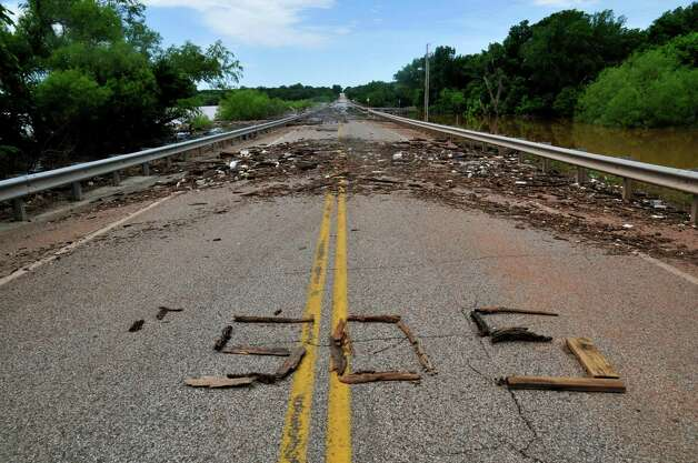 A messege spelled with debris sits on the Twin Bridges as water recedes from Lake Thunderbird Tuesday, May 26, 2015, after heavy rains hit Norman, Okla., over the weekend. (Kyle Phillips / The Norman Transcript via AP) ORG XMIT: OKNOT102 Photo: Kyle Phillips / The Norman Transcript