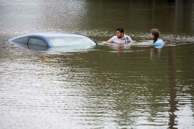 Roberto Salas, left, and Lewis Sternhagen check a flooded car on the frontage road between South Loop West Freeway and South Post Oak Road near the Willow Waterhole Bayou, Tuesday, May 26, 2015, in Houston. Floodwaters kept rising Tuesday across much of Texas as storms dumped almost another foot of rain on the Houston area, stranding hundreds of motorists and inundating the highways. (Marie D. De Jesus/Houston Chronicle via AP) ORG XMIT: TXHOU110 Photo: Marie D. De Jesus / Houston Chronicle