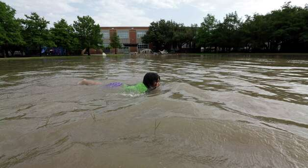 Joselyn Ramirez swims in a flooded school playground in Houston, Tuesday, May 26, 2015. Severe weather in the Houston area overnight caused flooding. (AP Photo/David J. Phillip) ORG XMIT: TXDP110 Photo: David J. Phillip / AP