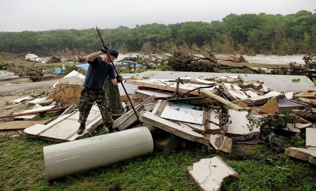 Kevin Calaway pries apart debris from a cabin shattered from a flood days earlier at a resort along the Blanco River, Tuesday, May 26, 2015, in Wimberley, Texas. Recovery teams were searching for as many as 12 members of two families who are missing after a rain-swollen river in Central Texas carried a vacation home off its foundation, slamming it into a bridge downstream. The hunt for the missing picked up after a holiday weekend of terrible storms that dumped record rainfall on the Plains and Midwest, caused major flooding and spawned tornadoes and killed at least eight people in Oklahoma and Texas. (AP Photo/Elaine Thompson) ORG XMIT: TXET103 Photo: Elaine Thompson / AP