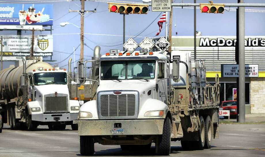 Oil and gas industry trucks crowd the intersections in Carrizo Springs near fast-food restaurants crowded with oil-field workers in early 2014 before falling oil prices slowed activity in the area. Photo: Bob Owen /San Antonio Express-News / © 2012 San Antonio Express-News