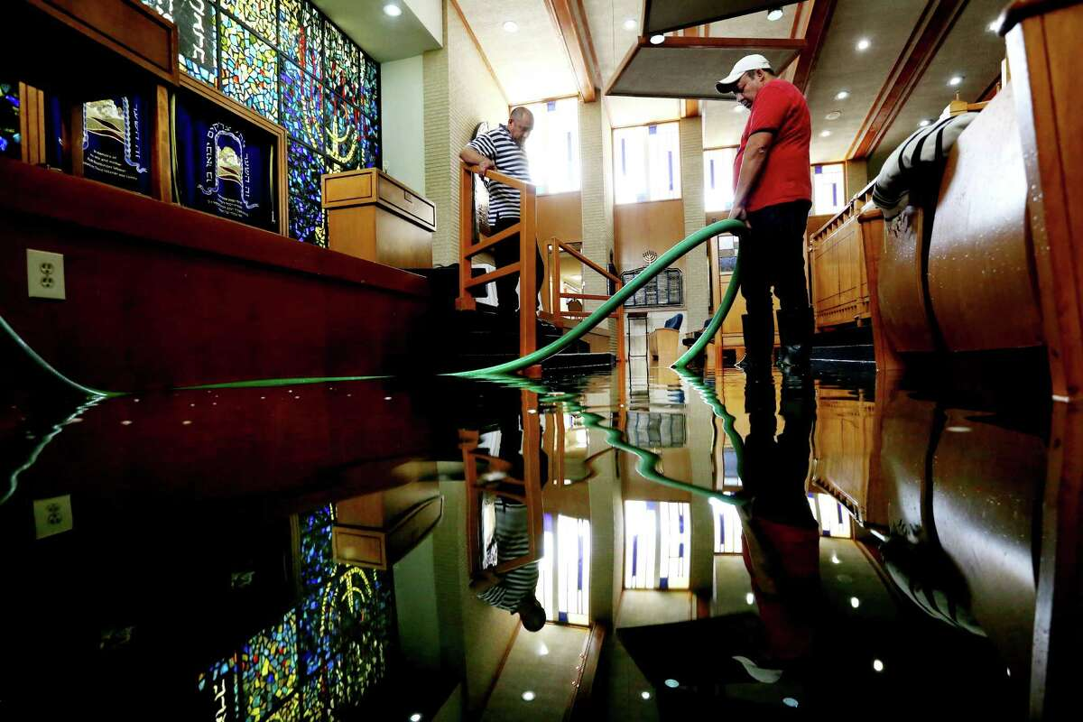 Wilber Albarenga, left, and Alfredo Chavez, pump water from the United Orthodox Synagogues that suffered extensive flood damage.