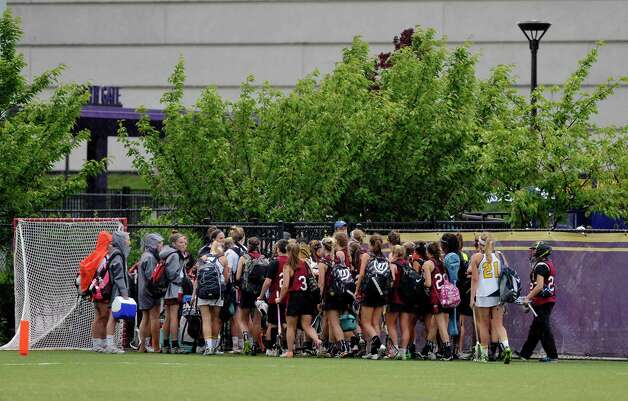 Players from Scotia-Glenville and Albany Academy for Girls make their way off the field for the night after their game was called off at the University at Albany during the High School Girls Section 2 Lacrosse Championships on Wednesday, May 27, 2015, in Albany, N.Y.  Due to weather all games were moved to Thursday.    (Paul Buckowski / Times Union)