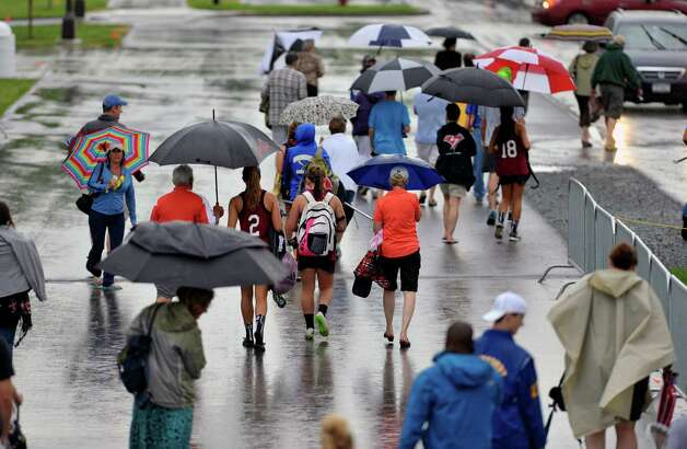 Parents and fans and players from Section 2 teams make their way to their vehicles in the rain at the University at Albany during the High School Girls Section 2 Lacrosse Championships on Wednesday, May 27, 2015, in Albany, N.Y.  Due to weather all games were moved to Thursday.    (Paul Buckowski / Times Union)