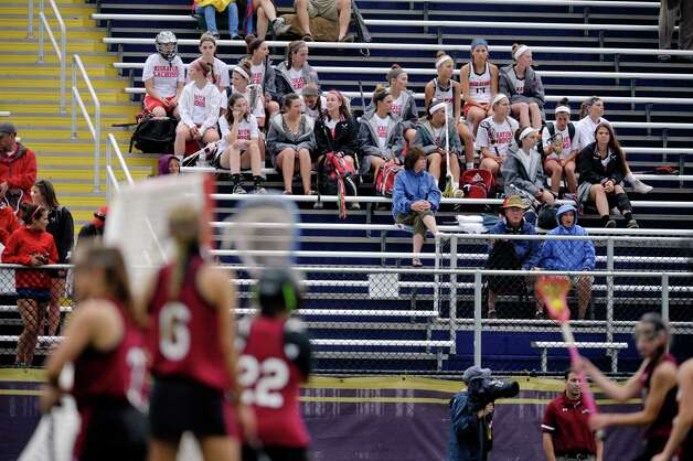 Members of the Niskayuna High School girls team watch from the stands as players from Scotia-Glenville warm up after a lightning delay at the University at Albany during the High School Girls Section 2 Lacrosse Championships on Wednesday, May 27, 2015, in Albany, N.Y.  Due to weather all games were moved to Thursday.    (Paul Buckowski / Times Union)