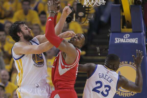 Golden State Warriors' Andrew Bogut and Houston Rockets' Dwight Howard get tangled up under the Houston basket in the first period  during Game 5 of the Western Conference Finals on Wednesday, May 27, 2015 in Oakland, Calif.