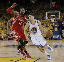 Golden State Warriors' Klay Thompson gets past Houston Rockets' Dwight Howard in the first period during Game 5 of the Western Conference Finals on Wednesday, May 27, 2015 in Oakland, Calif.