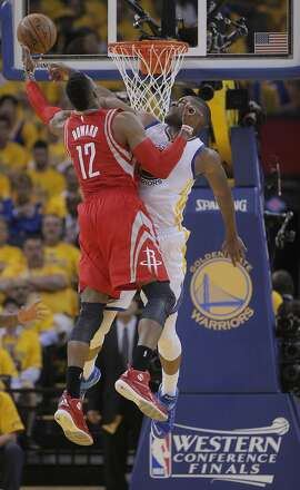 Golden State Warriors' Festus Ezeli  defends against Houston Rockets' Dwight Howard in the second period during Game 5 of the Western Conference Finals on Wednesday, May 27, 2015 in Oakland, Calif.