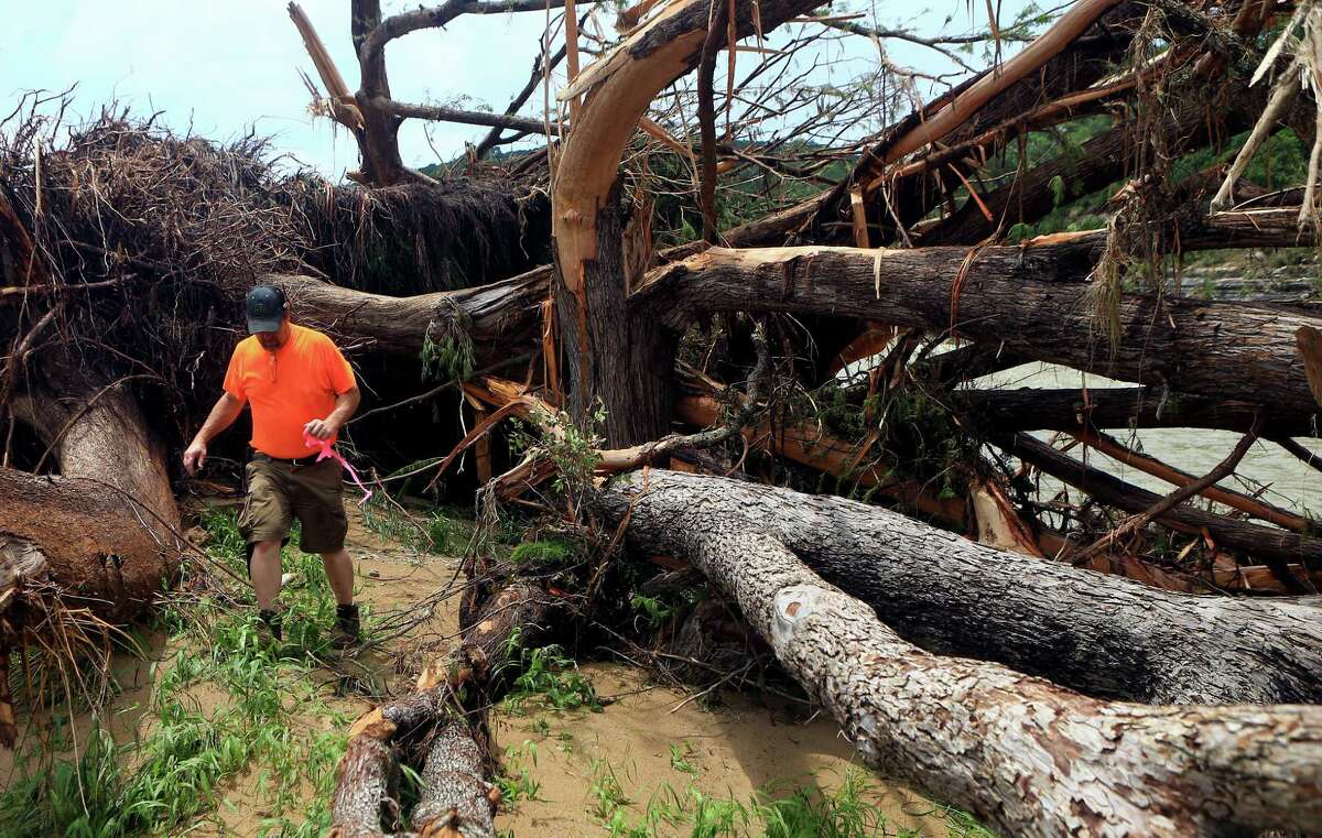 John Charba, a member of a search and rescue team, checks around a fallen tree Wednesday for people missing after heavy flooding near Umphery Ranch between Wimberley and San Marcos.