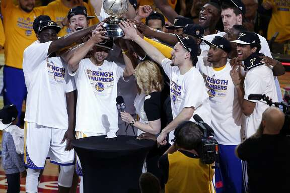 Golden State Warriors' Stephen Curry and teammates hold Western Conference trophy after defeating Houston Rockets 104-90 in Game 5 of NBA Playoffs' Western Conference Finals at Oracle Arena in Oakland, Calif., on Wednesday, May 27, 2015.