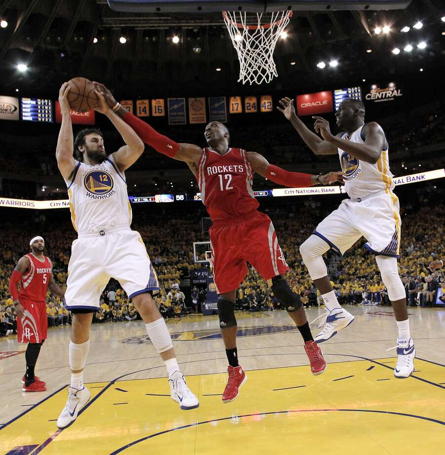 Andrew Bogut (12) pulls in a rebound ahead of Dwight Howard (12) in Game 5 of the NBA Western Conference Final at Oracle Arena in Oakland, Calif., on Wednesday, May 27, 2015. The Warriors defeated the Rockets 104-90 to advance to the NBA Finals against Cleveland Cavaliers. Photo: Carlos Avila Gonzalez, The Chronicle