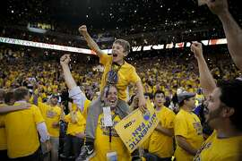 Zachary, 9, and Ken Trauner celebrate the Golden State Warriors' 104 to 90 victory over the Houston Rockets after Game 5 of the Western Conference Finals on Wednesday, May 27, 2015 in Oakland, Calif.
