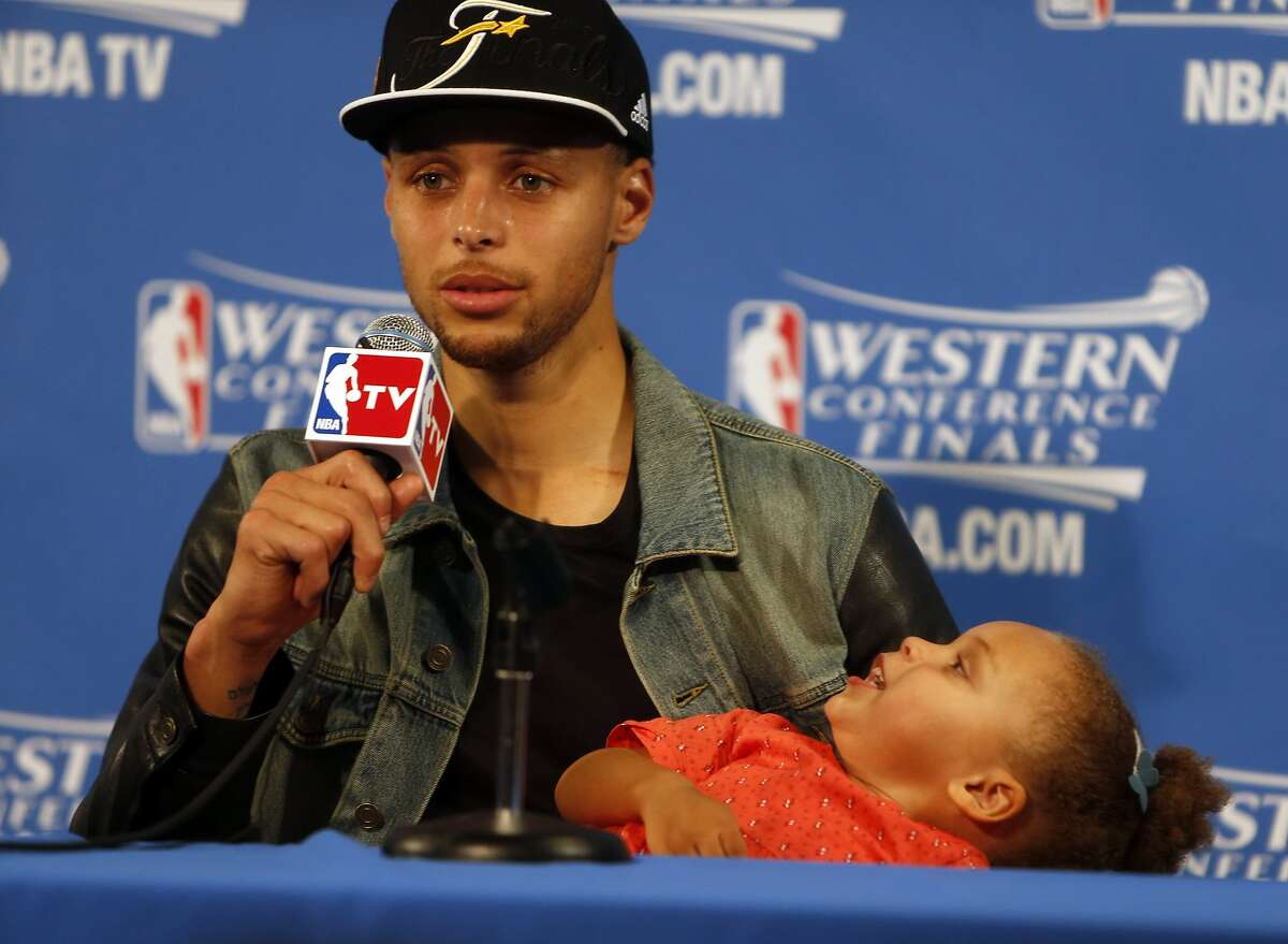 Golden State Warriors' Stephen Curry speaks to the media as his daughter Riley plays after Warriors' 104-90 win over Houston Rockets in Game 5 of NBA Playoffs' Western Conference Finals at Oracle Arena in Oakland, Calif., on Wednesday, May 27, 2015.