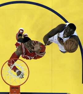 Draymond Green (23) shoots while defended by Dwight Howard (12) in Game 5 of the NBA Western Conference Final at Oracle Arena in Oakland, Calif., on Wednesday, May 27, 2015. The Warriors defeated the Rockets 104-90 to advance to the NBA Finals against the Cleveland Cavaliers.
