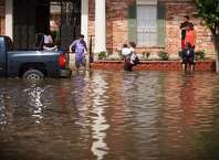 Residents of a flooded apartment complex cross a flooded street in Houston, May 26, 2015 after over 10 inches of rain fell, causing flooding. The rain virtually paralyzed parts of the city, and the storms killed at least eight people in Texas and Oklahoma. (Michael Stravato/The New York Times) ORG XMIT: XNYT147