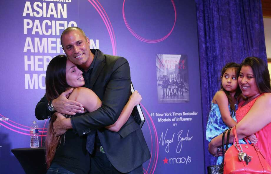 Gabby Aguilar receives a hug from famed fashion photographer Nigel Barker while sister Blanca Aguilar carries Sophia Rodriguez. Photo: Mayra Beltran, Houston Chronicle / © 2015 Houston Chronicle