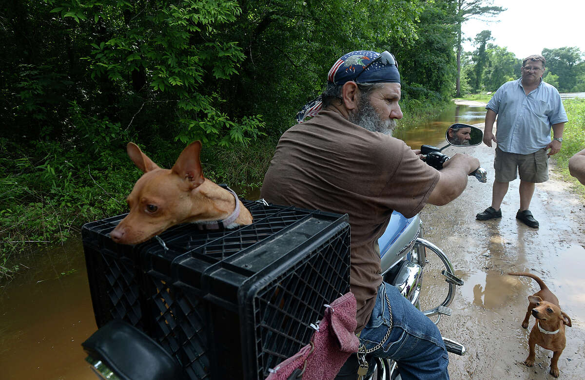 Shorty Kelly (left) and neighbor Charlie Marley (right) talk as he stops to observe the swelling Neches River, which had already begun to makes its way across Readman Road in southern Tyler County. Kelly and his dog Red were leaving their home for a couple of days to avoid expected problems of flooding. The gates of the Town Bluff dam on Steinhagen Lake were opened to relieve water levels, which added water to the already swollen Neches River running south of the dam. The river level currently stands at 71 1/2 feet, and is expected to rise another foot by Wednesday night. Residents of riverfront communities, including Marley, are evacuating or considering doing so as they anticipate further flooding throughout the area. Photo taken Wednesday, May 27, 2015 Kim Brent/The Enterprise