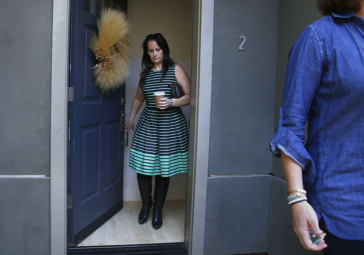 Home buyer Susan Giddens (left) and her agent Linnette Edwards (right) walk out of the front door of a home recently bought in Oakland, California, on Wednesday, May 27, 2015. Giddens toured the property two weeks ago for ten minutes before making an offer, with this being her first view of the property since.