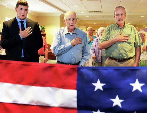 WWII Army veteran Francis Miner, center, is joined by his grandson Edward Hole, left, of Portsmouth, RI, and son William Miner of Pitcairn, NY, for the Pledge of Alligence during a ceremony to award Francis the POW Medal at Judson Meadows Assisted Living Community Wednesday May 27, 2015, in Glenville NY.  (John Carl D'Annibale / Times Union) Photo: John Carl D'Annibale / 00031983A