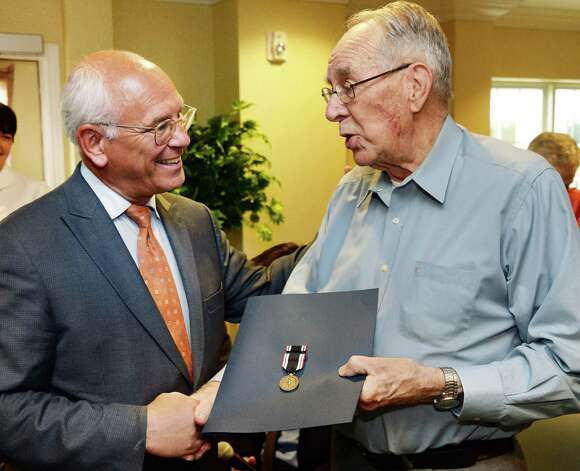 Congressman Paul Tonko, left, presents WWII Army veteran Francis Miner with the POW Medal during a ceremony at Judson Meadows Assisted Living Community Wednesday May 27, 2015, in Glenville NY.  (John Carl D'Annibale / Times Union) Photo: John Carl D'Annibale / 00031983A