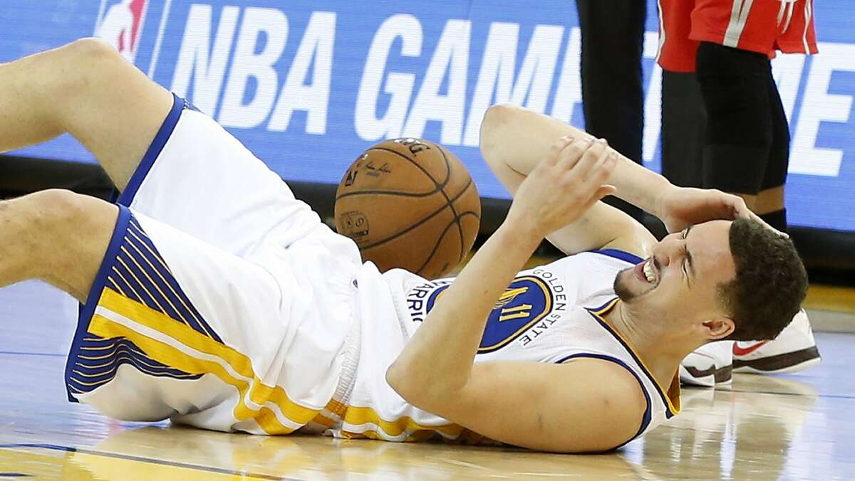 Golden State Warriors guard Klay Thompson holds his ear after he was hit on the side of the head by Houston Rockets forward Trevor Ariza during the fourth quarter of Game 5 of the NBA Western Conference finals at Oracle Arena Wednesday, May 27, 2015, in Oakland. ( James Nielsen / Houston Chronicle )