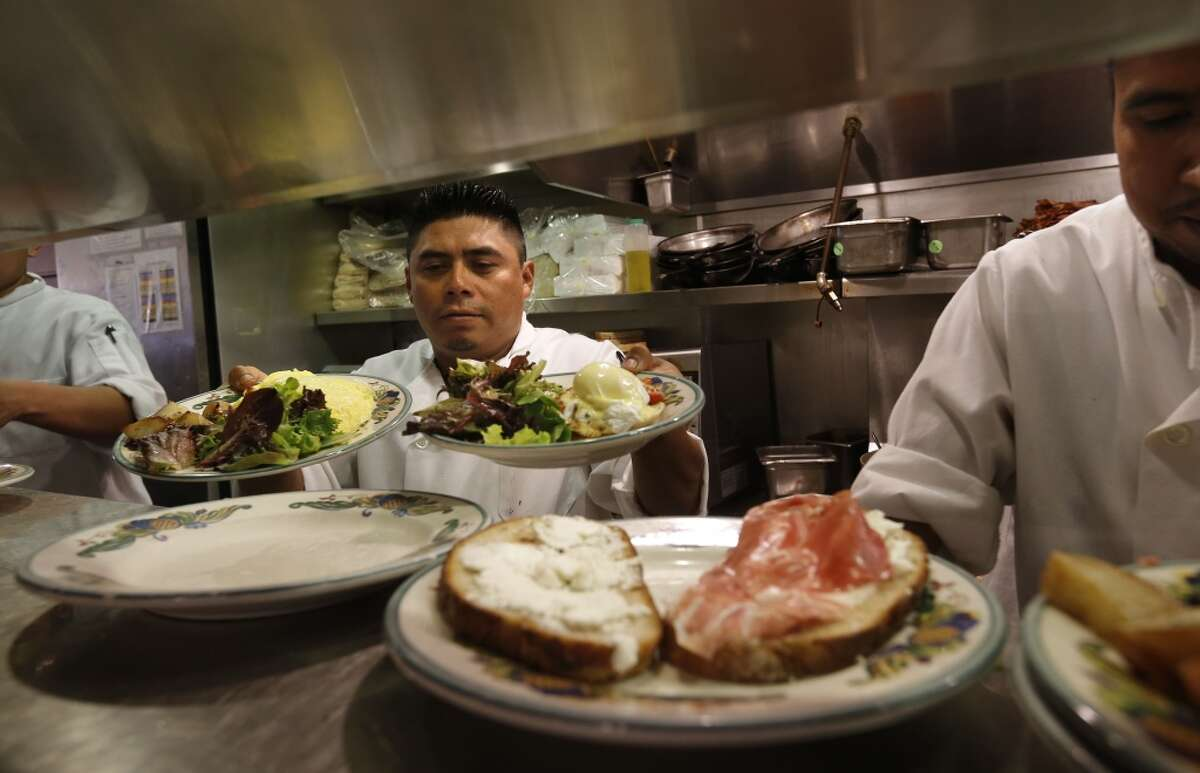 Cook Carlos Cauich prepares orders at Zazie restaurant, in San Francisco, Calif., on Wednesday Aug. 27, 2014.