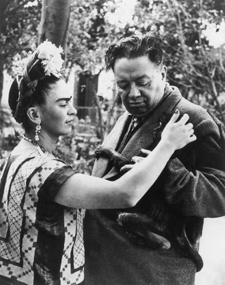 Mexican artist Frida Kahlo (1907-1954) pets a monkey,  clinging to the jacket of her husband, Mexican artist Diego Rivera (1886-1957). Photo: Wallace Marly, Getty Images